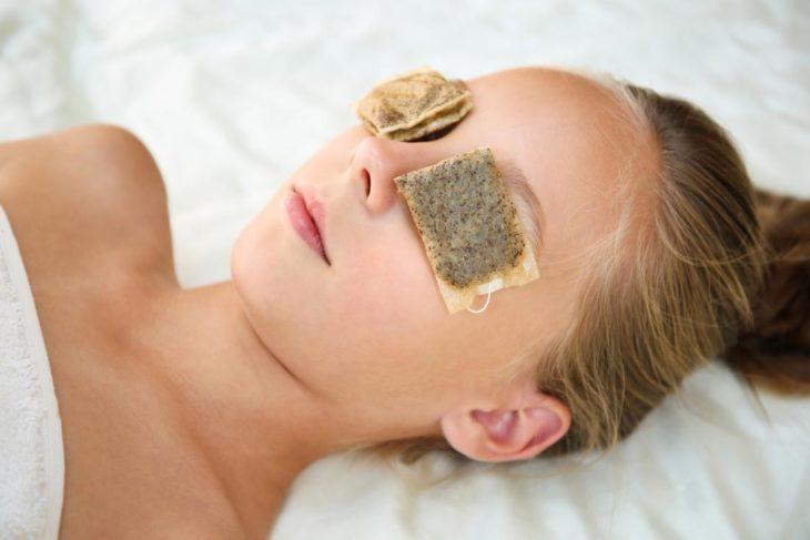 Chica con bolsas de té en los ojos para evitar el efecto de ojos cansados