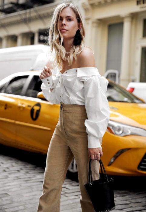 Outfit con blusa blanca; mujer rubia en la calle esperando taxi, con camisa sin hombros