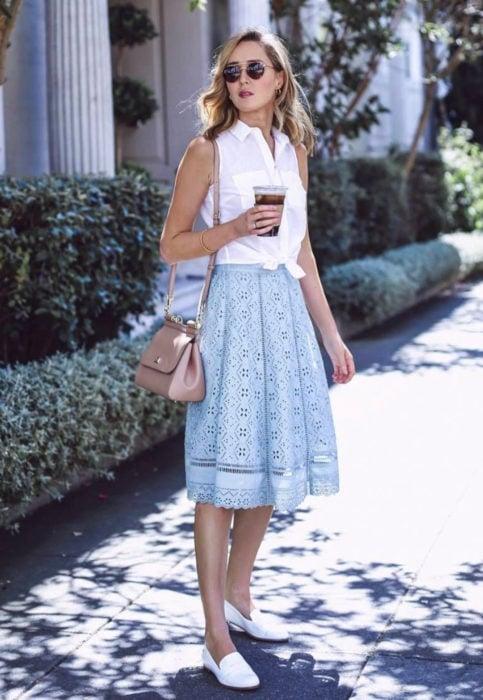 Outfit con blusa blanca; mujer rucia con camisa blanca sin mangas y falda azul con flats