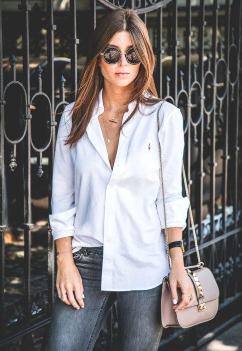 Outfit con blusa blanca; mujer cabello castaño y lacio, con lentes de sol redondos, camisa desfajada y bolsa beige con estoperoles