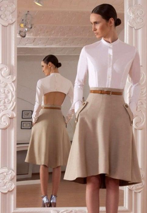 Outfit con blusa blanca; mujer mirándose al espejo, con peinado de chongo elegante, camisa blanca sin espalda, falda beige