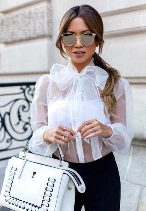 Outfit con blusa blanca transparente y top debajo; mujer con peinado de cola de caballo con lentes de sol