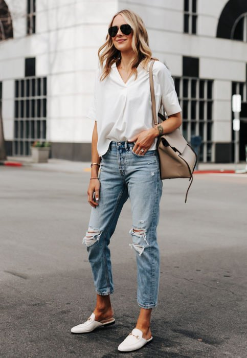 Outfit con blusa blanca; mujer rubia en la calle con mom jeans desgastados
