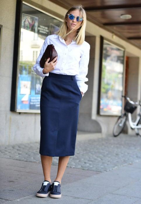 Outfit con blusa blanca; mujer de cabello rubio a los hombros, con falda lápiz y tenis