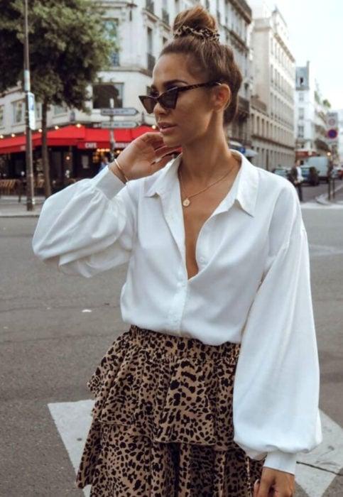 Outfit con blusa blanca; mujer en la calle, estilo retro, lentes triangulares, chongo alto, falda de animal print