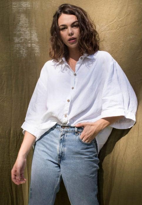 Outfit con blusa blanca; mujer castala de cabello corto y ondulado, camisa oversized