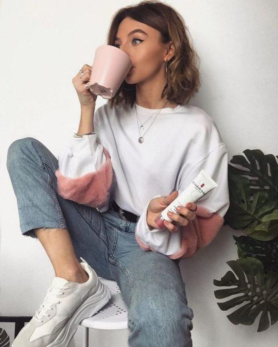 Chica de cabello corto viste una sudadera blanca con rosa y jeans