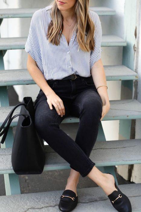 Chica rubia usa blusa de rayas azules con blanco y pantalón negro