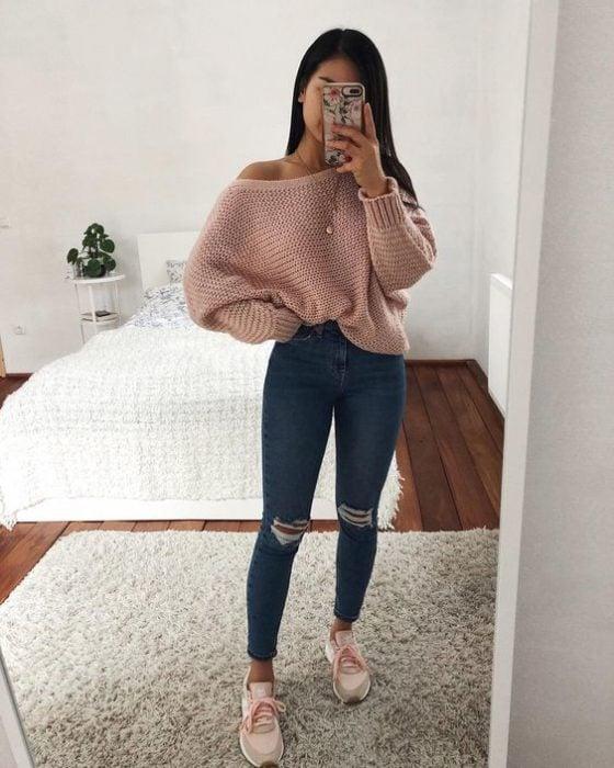 Chica morena de cabello largo toma selfue con jeans y suéter rosa palo