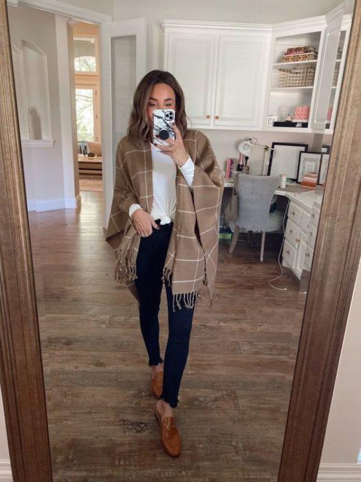 Mujer toma selfie con cardigan café con rayas blancas y pantalón negro