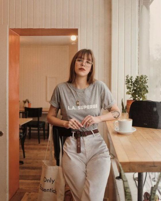 Chica con pantalón de tela ligera beige y playera gris