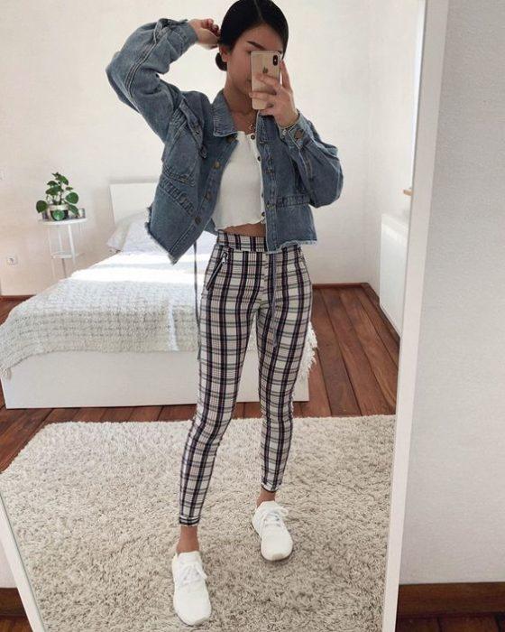 Chica se toma selfie frente al espejo con pantalín a cuadros, blusa blanca y chaqueta de mezclilla