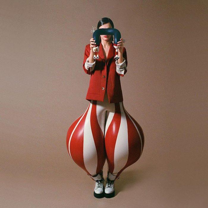 Chica usando unos pantalones en blanco y rojo hechos de látex y con la apariencia de un globo