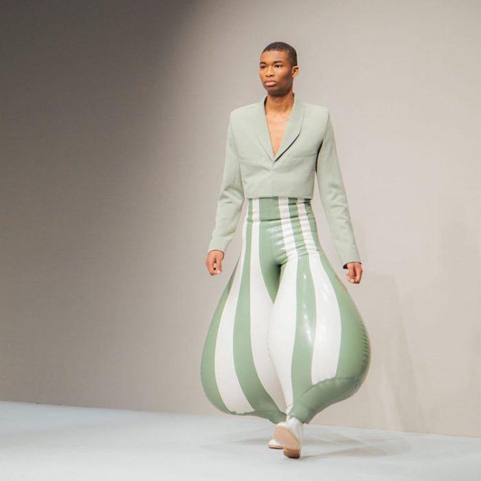 Chico usando unos pantalones en blanco y verde hechos de látex y con la apariencia de un globo
