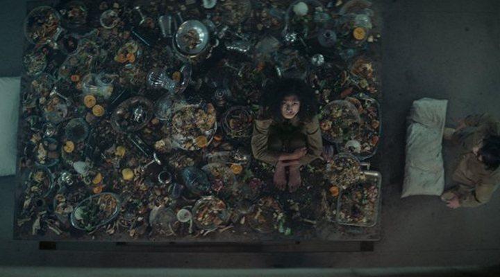 Escena de la película El Hoyo en la que aparece una mujer sentada sobre comida