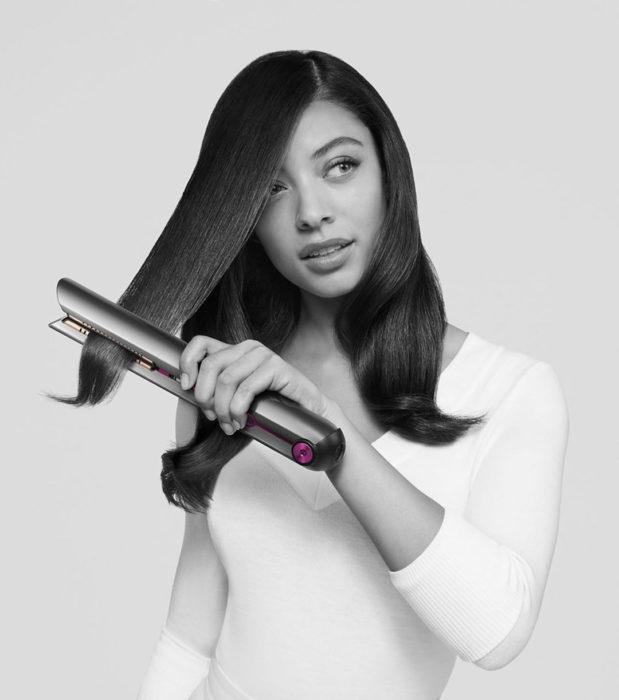 Chica planchando su cabello con la plancha Dyson Corrale