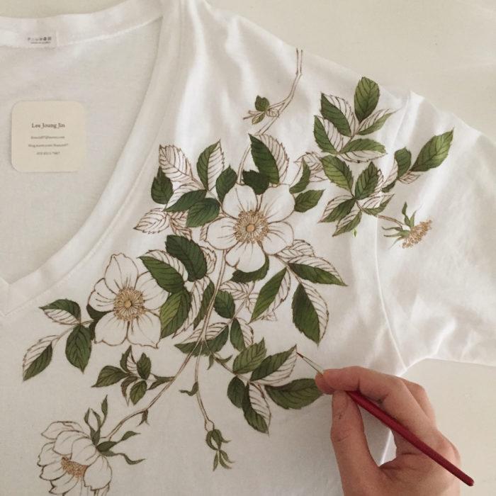 Camiseta blanca con hojas verdes y flores blancas