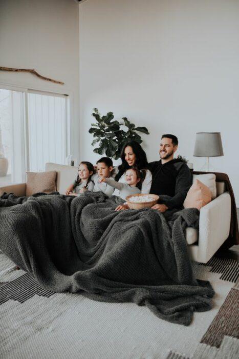 Familia recostada en la cama mientras ven películas