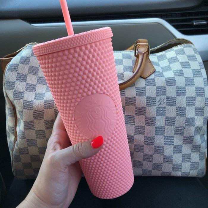 Chica sosteniendo un vaso rosa de starbuck