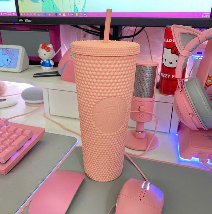 Vaso rosa de Starbucks sobre una mesa de computadoras