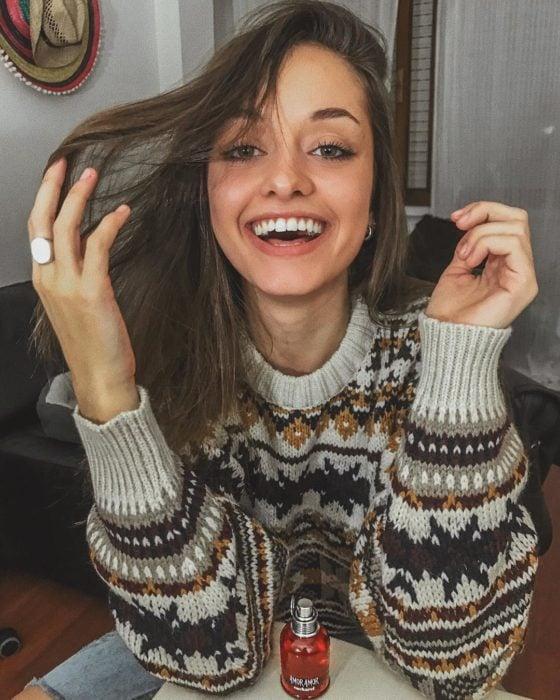 CHica sonriéndo usando suéter con cuello redondo