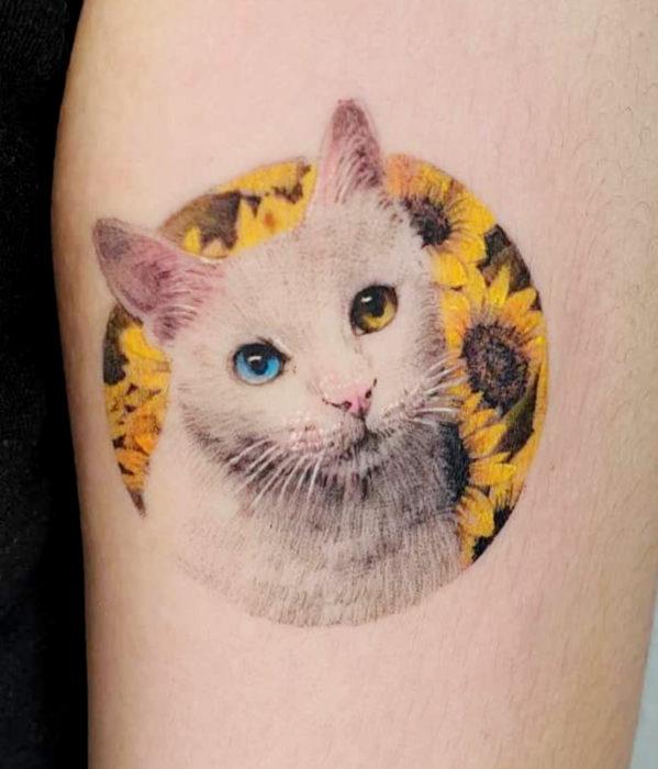 Tatuajes femeninos y con significado; gato blanco con ojos azul y amarillo, en flores girasoles
