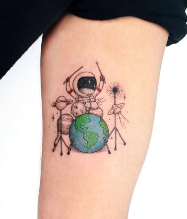 Tatuajes femeninos y con significado; astronauta baterista en el brazo
