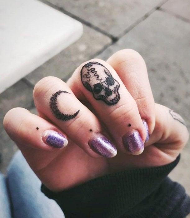 Tatuajes femeninos y discretos en las manos; luna y cráneo en puntillismo