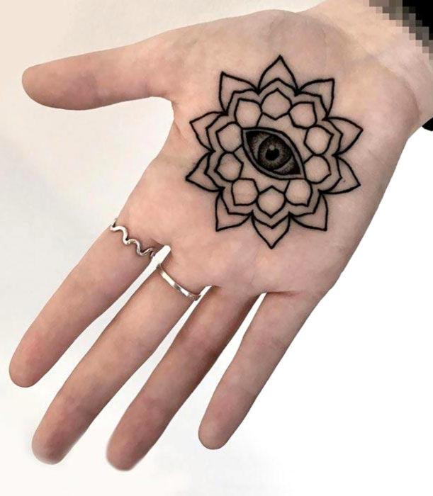Tatuajes femeninos y discretos en las manos; flor de loto con ojo en la palma de la mano