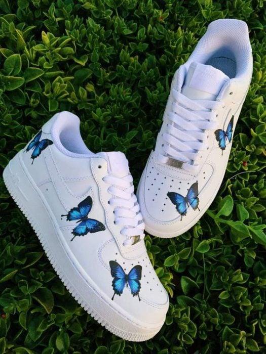 Tenis blancos con dibujos de mariposas azules a los costados