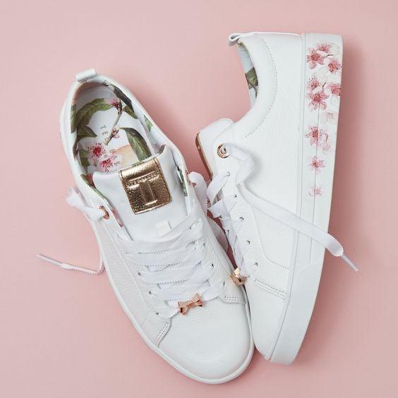 Tenis blancos con flores en rosa en los costados de la suela