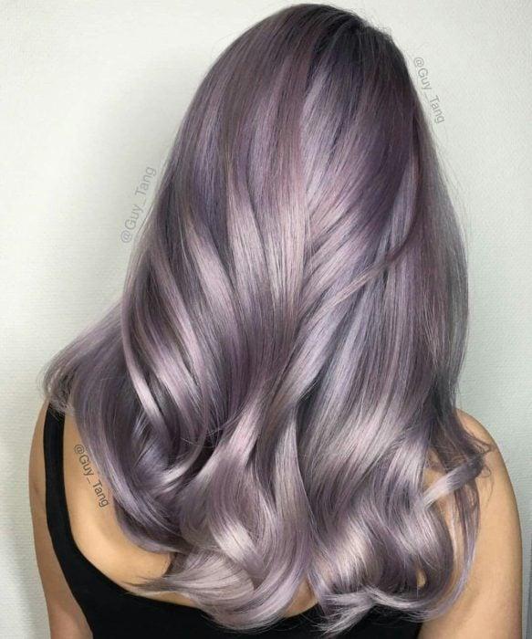 Chica con el cabello teñido de color morado con tintes de color gris