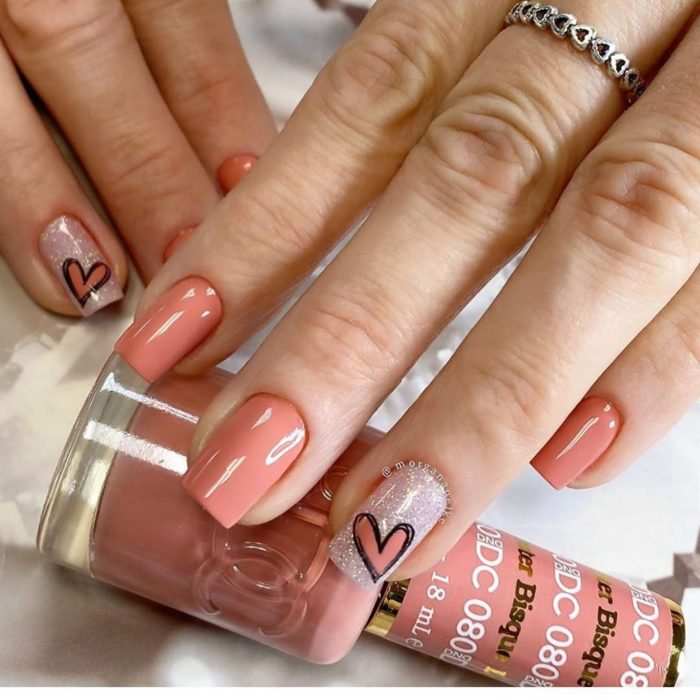 Manicura color salmon con dedo anular en brillo y decorado