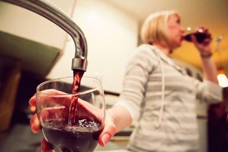 Mujer tomando vino que sale del grifo de su casa