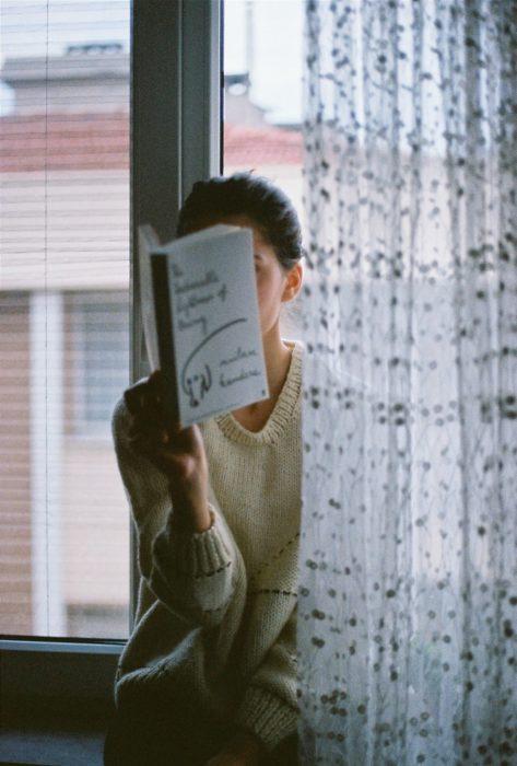 Mujer leyendo en la ventana de su casa
