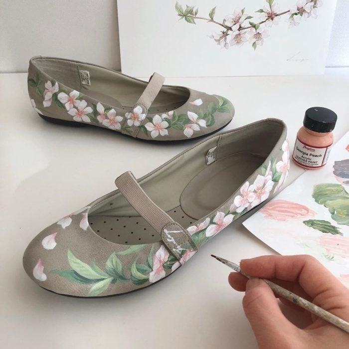 Zapatos tipo ballerinas en tono verde olivo, con hojas verdes y flores de árbol de cerezo tono rosado
