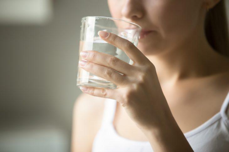 Chica usando como enjuague bucal agua oxigenada con agua natural