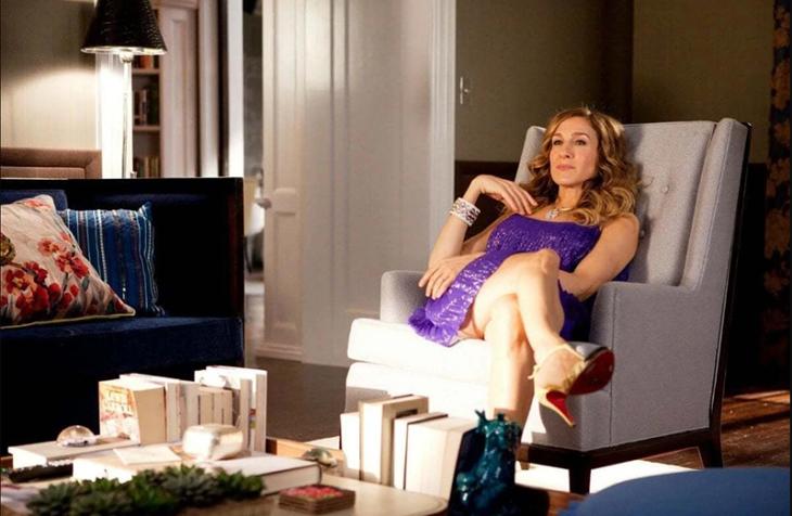 Carrie Bradshaw sentada en el sofá con vestido morado