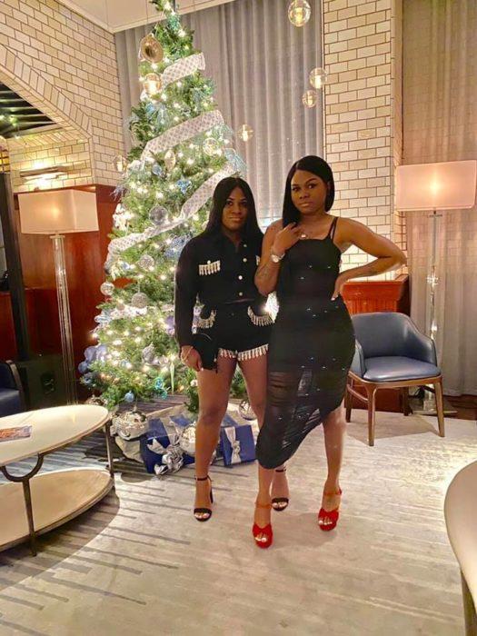 Ashley Thomas y Toya Wimberlyposando frente a un pino de Navidad