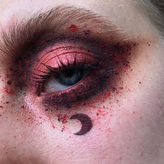 Maquillaje en sobra para ojos en tonos rojos y negros con decorado de luna