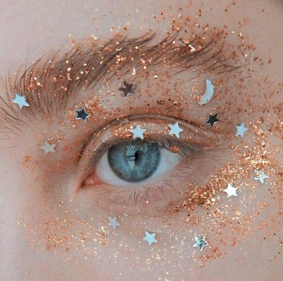 Maquillaje en tono dorado con glitters y estampillas de estrellas plateadas