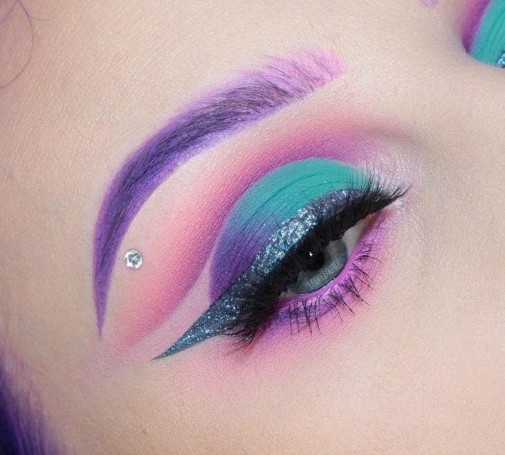 Maquillaje en colores verde, morado y rosa fucsia inspirado en el espacio