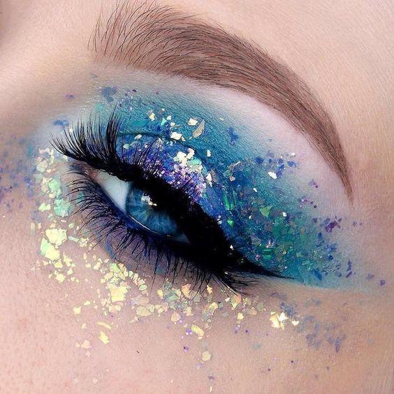 Maquillaje de sombra en azul,, morado y glitters metalizado