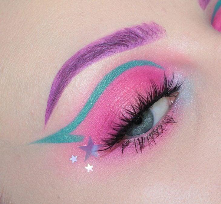 Sombra para ojos en tono rosa fucsia con verde y morado en efecto neón