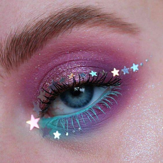 Sombra para ojos en tono moraro con rimel verde menta y delineado de estrellas