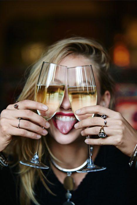 Chica con dos copas de champagne frente al rostro