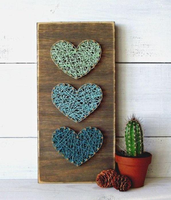 DIY de trozo de madera y clavos y estambre que forma corazones de diferentes colores