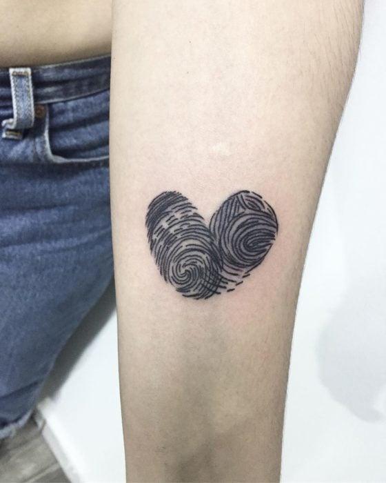 Tatuaje de madre e hija, de un corazón formado con las huelas dactilares