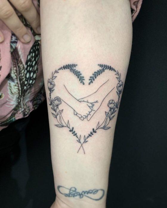 tatuaje madre e hija, agarrandose las manos y un corazón al rededor de ella