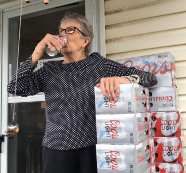 Abuelita recargada en paquetes de cerveza cerrados